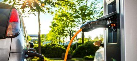 Elektroautos an Ladestation auf Firmengelände im Gegenlicht – Electric Car at Charging Station