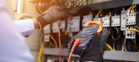 Elektroingenieur, der ein digitales Multimeter verwendet, um die aktuelle Spannung am Leistungsschalter im Hauptverteiler zu überprüfen.