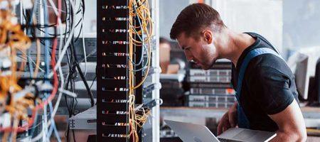 Junger Mann in Uniform und mit Laptop arbeitet mit Internetgeräten und Kabeln im Serverraum